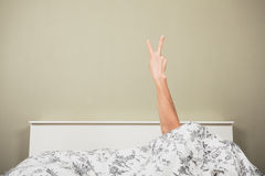 Woman in bed displaying obscene gesture Stock Image