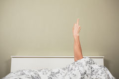 Woman in bed displaying obscene gesture Stock Images
