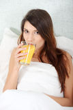 Woman in bed drinking orange juice Royalty Free Stock Photography