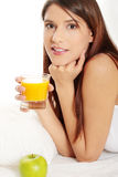 Woman in bed drinking orange juice Stock Image