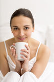 Woman in bed drinking tea Stock Photography