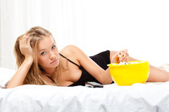 Woman on bed eating popcorn Royalty Free Stock Photography