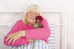 Woman in bed embracing a rose Stock Image