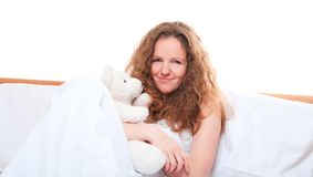 Woman in bed embracing teddy bear Stock Photography