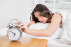 Woman in bed extending hand to alarm clock Royalty Free Stock Photo