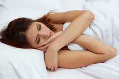 Woman on bed with extreme stress. Sick woman frowning on bed with extreme stress Stock Photo