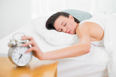 Woman in bed with eyes closed extending hand to alarm clock Royalty Free Stock Image