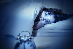 Woman in bed with eyes opened suffering insomnia and sleep disorder. Young woman in bed with alarm clock and eyes opened suffering insomnia and sleep disorder Stock Image