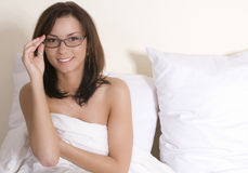 Woman on bed with glasses. Attractive brunette naked on a white linen bed with glasses on Royalty Free Stock Photography