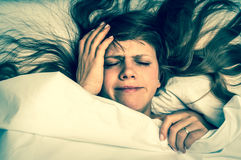 Woman in bed having headache in the morning - retro style Stock Photo