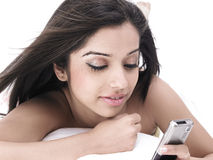 Woman in bed with her cell phone Stock Photography