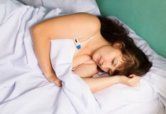 Woman on the bed  the high fever Royalty Free Stock Photos