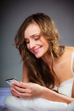 Woman on bed holding mobile phone. Royalty Free Stock Image