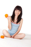 Woman on bed holding orange Stock Image