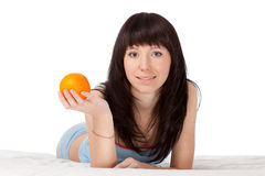 Woman on bed holding orange Stock Photos