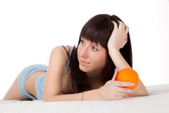 Woman on bed holding orange Royalty Free Stock Photo