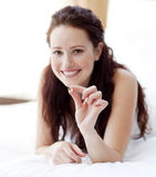 Woman in bed holding a pill Royalty Free Stock Images