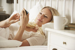 Woman In Bed At Home Texting On Mobile Phone Stock Photo