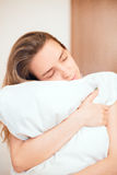 Woman in bed hugs pillow, sleeps or in love Royalty Free Stock Photos