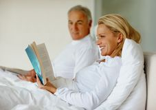 Woman in bed with husband reading a book Royalty Free Stock Photography