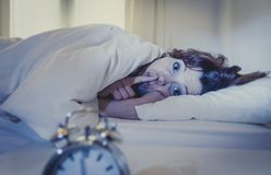 Woman in bed with insomnia that can't sleep because of noise. Woman with red hair in her bed with insomnia and can't sleep because of noise royalty free stock image