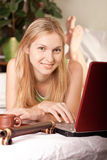 Woman in bed with laptop. Beautiful blond female in bed with her laptop Stock Photo