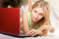 Woman in bed with laptop Stock Photos