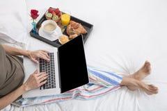 Woman bed laptop breakfast Stock Image