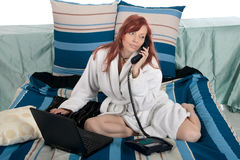 Woman bed laptop phone call Stock Image