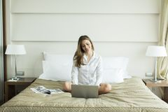 Woman in the bed with laptop Stock Image