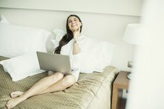 Woman in the bed with laptop Stock Photo