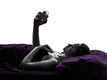 Woman in bed looking at alarm clock silhouette Stock Images