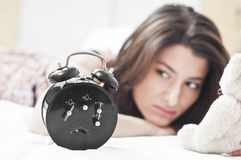 Woman on bed looking at a clock Stock Images