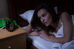 Woman in bed looking at clock Stock Photography