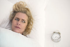 Woman in bed looking at her alarm clock Royalty Free Stock Photos