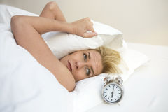 Woman in bed looking at her alarm clock Stock Photo