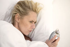 Woman in bed looking at her alarm clock Royalty Free Stock Photography