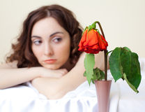 Woman in bed looking on the rose (focus on rose) Royalty Free Stock Photo