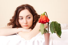 Woman in bed looking on the rose (focus on rose) Stock Photo