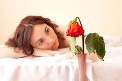 Woman in bed looking on the rose (focus on rose) Stock Photography