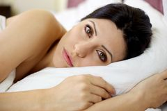 Woman in bed looking sad Stock Image