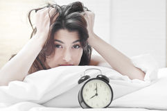 Woman on bed looking tired Royalty Free Stock Photos