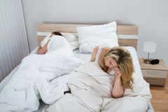 Woman on bed while man sleeping in bedroom Royalty Free Stock Photos