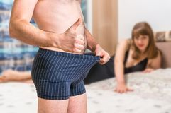 Woman in bed and man in underwear showing thumb up Royalty Free Stock Photo