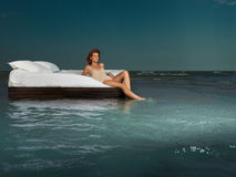 Woman in bed in middle of ocean Stock Images