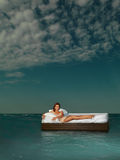 Woman in bed in middle of ocean Stock Photo