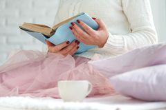 Woman on the bed with old book and cup of tea stock photos