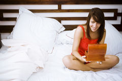 Woman in bed opening a present Stock Photography