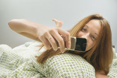 Woman in bed with phone Royalty Free Stock Image