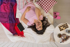 Woman in bed with phone Stock Image